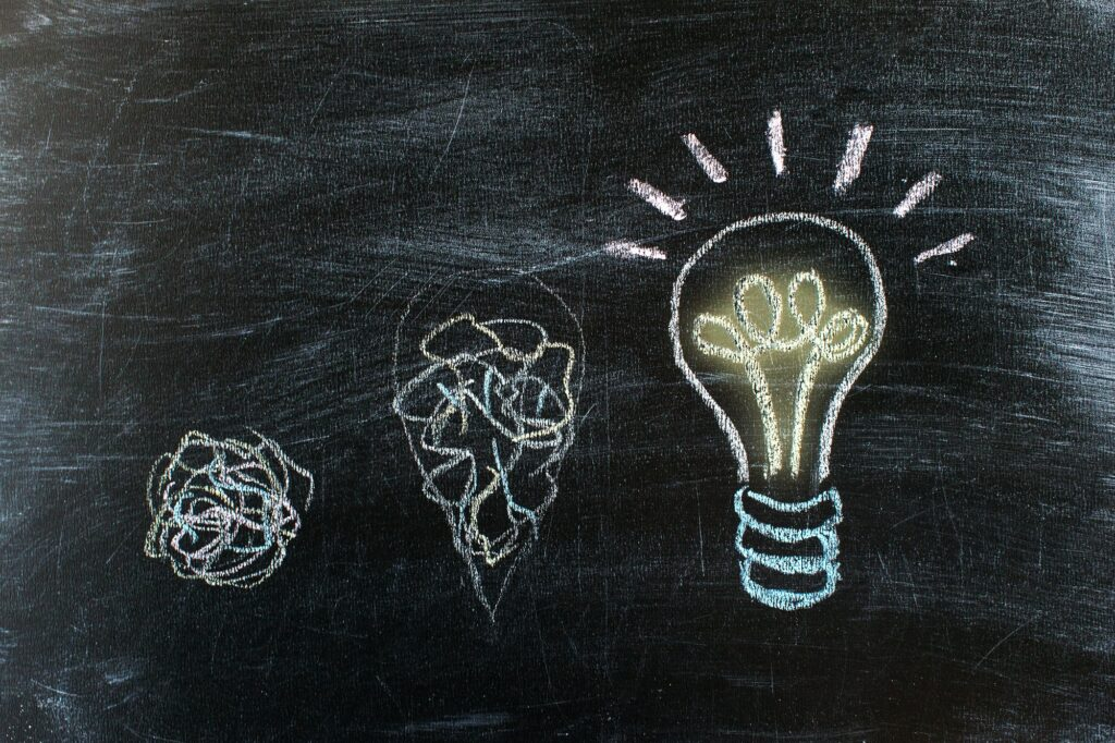 Chalkboard with Chalk Drawing of Hanging Light Bulb. Bright idea on blackboard concept. Way of